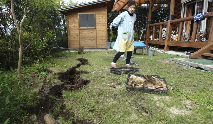 In this April 19, 2016 photo, Yachiyo Fuchigami, 64, wife of Koji Fuchigami, looks at the deep crack in the garden as the couple briefly returns home to check the extent of damage to their houses in Minamiaso, Kumamoto prefecture, Japan. A mountain village that attracted retirees, tourists and agriculture students to a college campus faces a grim future after last week's devastating earthquake. (AP Photo/Mari Yamaguchi)