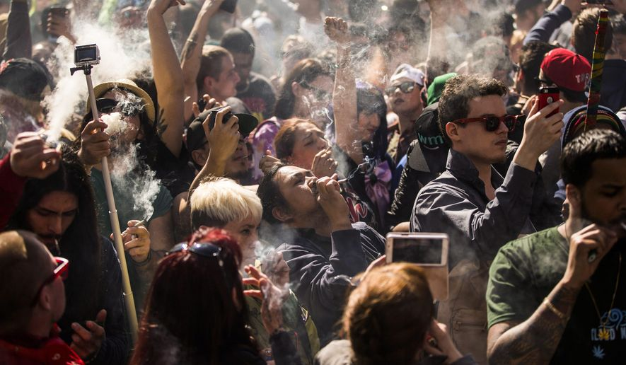 "People gather to smoke marijuana during the ""420 Toronto"" rally in Toronto on Wednesday, April 20, 2016. (Mark Blinch/The Canadian Press via AP)"