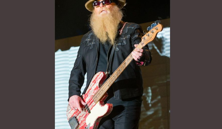 FILE - In this April 25, 2015 file photo, Dusty Hill of ZZ Top performs during the 2015 Stagecoach Festival at the EmpireClub in Indio, Calif. ZZ Top is postponing several dates on their tour after bass player Dusty Hill fractured his shoulder before a show last week in Texas. The rock band said in a statement on Wednesday, April 20, 2016, that concert dates through May 7 have been postponed as he recovers from his injury. (Photo by Paul A. Hebert/Invision/AP, File)