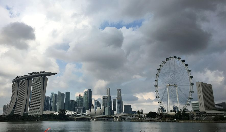 Two kayaks are dwarfed against the skyline of the Marina Bay area, which is home to popular hotels, and tourist attractions such as the Singapore Flyer, the city-state's observation wheel seen at right, on Wednesday, April 20, 2016, in Singapore. (AP Photo/Wong Maye-E)