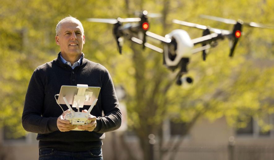 In this Thursday, April 14, 2016, photo, DroneLinx CEO Steve Metzman operates a drone to make videos and still images of an apartment building, in Philadelphia. DroneLinx, a service based in New York, takes shots of cellphone towers, bridges, oil rigs and utility lines that are difficult to get careful inspections of, Metzman says. (AP Photo/Matt Rourke)