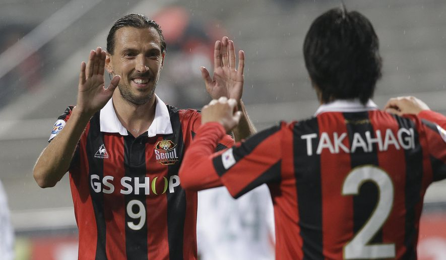 Dejan Damjanovic, left, of South Korea's FC celebrates with his teammate Yojiro Takahagi after scoring a goal against Thailand's Buriram United during their Group F soccer match in the AFC Champions League at Seoul World Cup Stadium in Seoul, South Korea, Wednesday, April 20, 2016. (AP Photo/Ahn Young-joon)