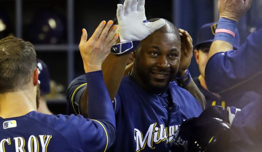 Milwaukee Brewers' Chris Carter is congratulated in the dugout after hitting a two-run home run during the seventh inning of a baseball game against the Minnesota Twins Wednesday, April 20, 2016, in Milwaukee. (AP Photo/Morry Gash)
