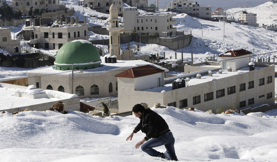 FILE - In this Dec. 15, 2013 file photo, a Palestinian walks through snow on his way home in the West Bank city of Nablus. The Boulder, Colo., City Council was scheduled to vote Tuesday, April 19, 2016, on a formal sister-city relationship with Nablus on the West Bank. But proponents instead asked the city to name a mediator to work with them and opponents, saying they were surprised by the resistance they encountered despite their efforts to win over their critics. (AP Photo/Nasser Ishtayeh, File)