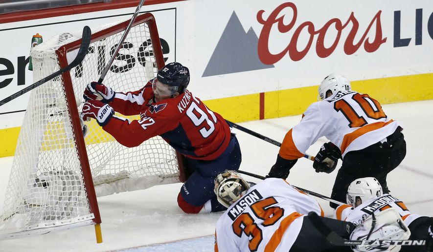 RETRANSMISSION TO CORRECT TO GAME 1 INSTEAD OF GAME2 - Washington Capitals center Evgeny Kuznetsov (92), from Russia, collides with the goal, with Philadelphia Flyers center Brayden Schenn (10) and goalie Steve Mason (35) nearby, during the third period of Game 1 of a first-round NHL hockey Stanley Cup playoff series Thursday, April 14, 2016, in Washington. The Capitals won 2-0. (AP Photo/Alex Brandon)