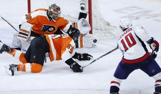 Philadelphia Flyers' Michal Neuvirth (30) and Andrew MacDonald (47) defend a shot by Washington Capitals' Mike Richards (10) during the third period of Game 4 in the first round of the NHL Stanley Cup hockey playoffs, Wednesday, April 20, 2016, in Philadelphia. Philadelphia won 2-1. (AP Photo/Matt Slocum)