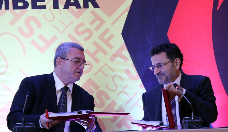 Albanian Football Federation Head Armand Duka, left, exchanges the signed documents for the new 22,300-seat national stadium Tirana, Thursday, April 21, 2016, with Idajet Ismailaj, owner of Albstar, the company that will build it. The new 50-million Euro (56.7 million US dollar) project, designed by Italian company Archea, is expected to be completed in three years. (AP Photo/Hektor Pustina)