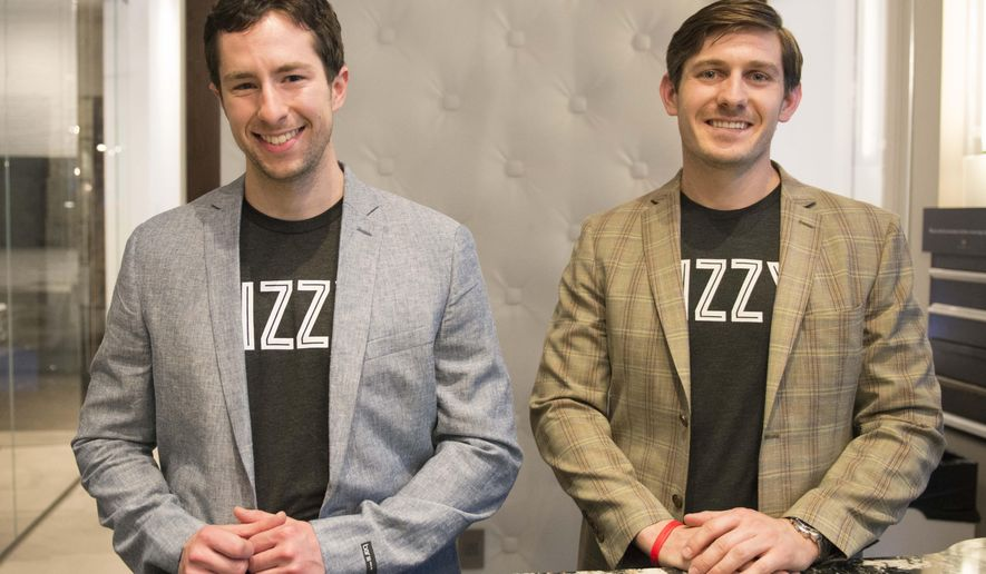 In this April 16, 2016, photo, co-founders of Bizzy Coffee Alex French, left, and Andrew Healy stand for a portrait at the official Bizzy Grand Launch Party at the Cambria Gallery in Minneapolis. (Niti Gupta/The Minnesota Daily via AP) MANDATORY CREDIT