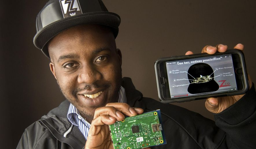 In this March 16, 2016 photo, Jamaal Crayton, of Peoria, Ill., shows a prototype of a ball cap that will feature a live display that allows the wearer to change the graphics on the hat in real-time, synced by Bluetooth to their phone. The Zero Wearables hat will eventually use a flexible paper display that can be built into the front of the hat. (Fred Zwicky/Journal Star via AP)  MANDATORY CREDIT