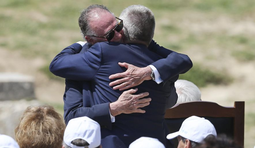 The President of the Rio 2016 Organizing Committee Carlos Nuzman hugs IOC President Thomas Bach during the ceremonial lighting of the Olympic flame in Ancient Olympia, Greece, Thursday, April 21, 2016. The flame will be transported by torch relay to the Brazilian city of Rio de Janeiro, which will host the 2016 Olympic Games. (AP Photo/Petros Giannakouris)