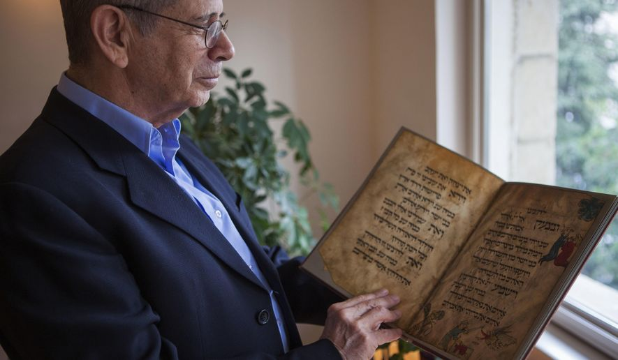 In this photo taken Wednesday, April 13, 2016, Eli Barzilai holds a copy of the Birds' Head Haggadah in his house in Jerusalem. Barzilai and his cousins, the grandchildren of one of the earliest Jewish victims of the Nazis, are laying claim to a jewel of Israel's leading museum: the world's oldest surviving illustrated Passover manuscript. The descendants of a German Jewish lawmaker say the famed Birds' Head Haggadah, a medieval copy of the text read around Jewish dinner tables on Passover, was stolen from their family during the Nazi era and sold without their consent to the predecessor of the Israel Museum in Jerusalem 70 years ago. (AP Photo/Dan Balilty)