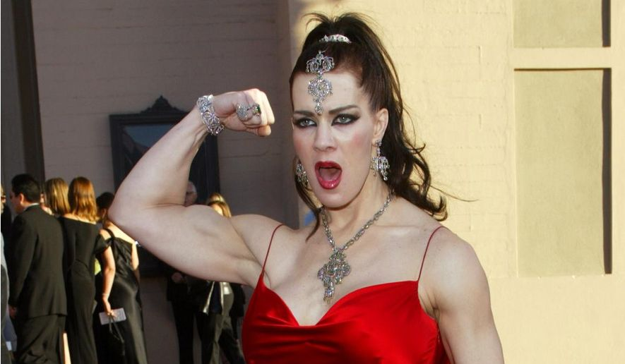 In this Nov. 16, 2003, file photo, Joanie Laurer, former pro wrestler known as Chyna, flexes her bicep as she arrives at the 31st annual American Music Awards, in Los Angeles. (AP Photo/Kevork Djansezian, File)