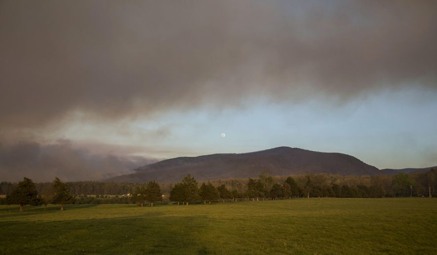 In this Wednesday, April 20, 2016 photo, smoke fills the sky as a forest fire burns in the Shenandoah National Park near Elkton, Va. Crews with the Virginia Department of Forestry worked Wednesday to contain the wildfire. (Michelle Mitchell/News-Virginian via AP) MANDATORY CREDIT