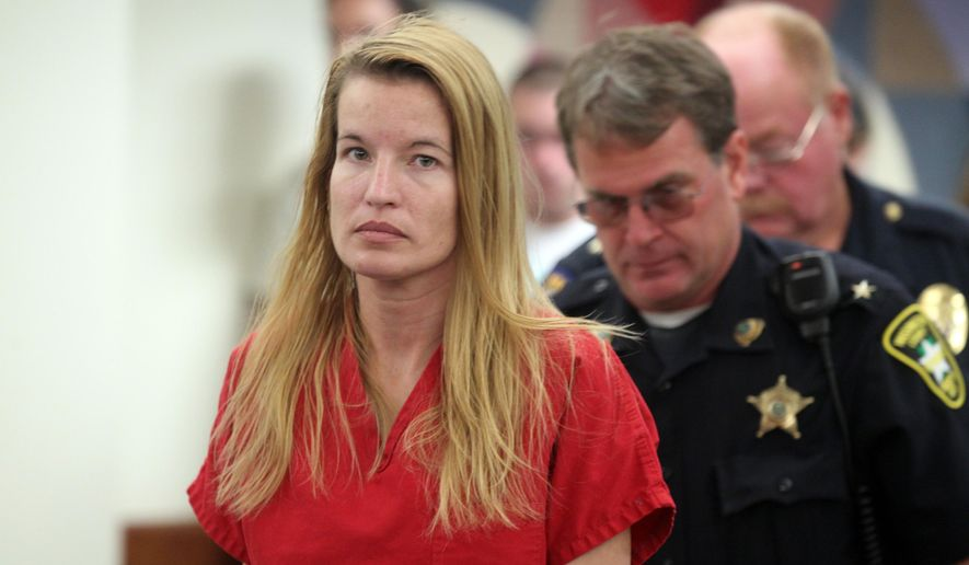 FILE- In this Aug. 10, 2015, file photo, Jody Herring is led out of court after her arraignment in Vermont Superior Court in Barre, Vt.  A lawyer for Herring, a Vermont woman charged with killing a social worker and three of her own relatives after losing custody of her daughter, says she's incompetent to stand trial. (Toby Talbot/Times Argus via AP, Pool, File)