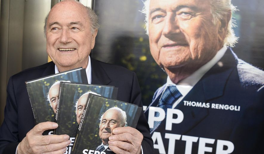 """Former FIFA president Sepp Blatter poses with copies of the book """"Sepp Blatter: Mission and Passion Football"""", during the book presentation in Zurich, Switzerland, Thursday, April 21, 2016. The book was written by his official spokesman Thomas Renggli. (Walter Bieri/Keystone via AP)"""