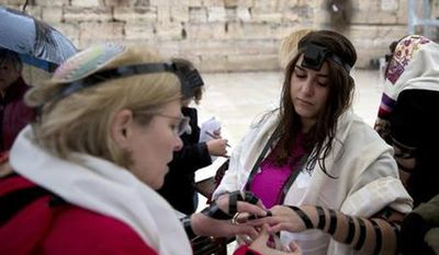 """In this Sunday, Feb. 7, 2016 file photo, Israeli women put on Tefillin also known as Phylacteries, a small leather box containing religious text usually worn by Jewish men, at the Western Wall, the holiest site where Jews can pray in Jerusalem's Old City. Israel's attorney general has banned Jewish women's prayer group called Women of the Wall from holding an all-female """"priestly blessing"""" next week and it is an unrecognized custom that has never been held at the Western Wall. (AP Photo/Sebastian Scheiner, File)"""