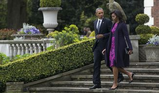 President Barack Obama and first lady Michelle Obama walk from Winfield House in London en route to Windsor Castle in Windsor, England, Friday, April 22, 2016, to meet with Britain's Queen Elizabeth II and Prince Philip. (AP Photo/Carolyn Kaster)