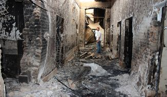 FILE - In this Oct. 16, 2015, file photo, an employee of Doctors Without Borders stands inside the charred remains of their hospital after it was hit by a U.S. airstrike in Kunduz, Afghanistan. The U.S. military is acknowledging that its airstrikes killed 20 civilians in Iraq and Syria over a five-month period that began last September. Central Command announced the results of multiple investigations of claims of civilian deaths from airstrikes aimed at Islamic State targets between Sept. 10, 2015 and Feb. 2, 2016. Six of the strikes were in Iraq and three were in Syria. (Najim Rahim via AP, File)