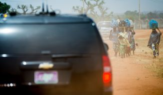 The motorcade carrying U.S. Ambassador to the United Nations Samantha Power passes people walking along a dirt road as she travels to visit the Malkohi Internally Displaced Person Camp in Yola, Nigeria, Friday, April 22, 2016. Power is traveling to Cameroon, Chad, and Nigeria to highlight the growing threat Boko Haram poses to the Lake Chad Basin region. (AP Photo/Andrew Harnik)