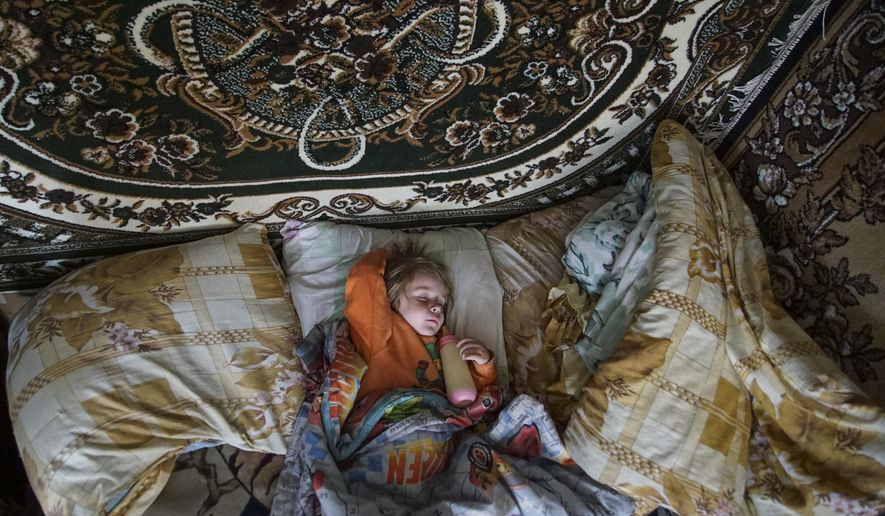 In this photo taken on Tuesday, April  5, 2016, Natalya Vetrova, one year old, sleeps holding a bottle with fresh cow milk at home in Zalyshany, 53 km (32 miles) southwest of the destroyed reactor of the Chernobyl plant, Ukraine. Her village is in one of the sections of Ukraine contaminated by radioactive fallout from the Chernobyl nuclear explosion. (AP Photo/Mstyslav Chernov)