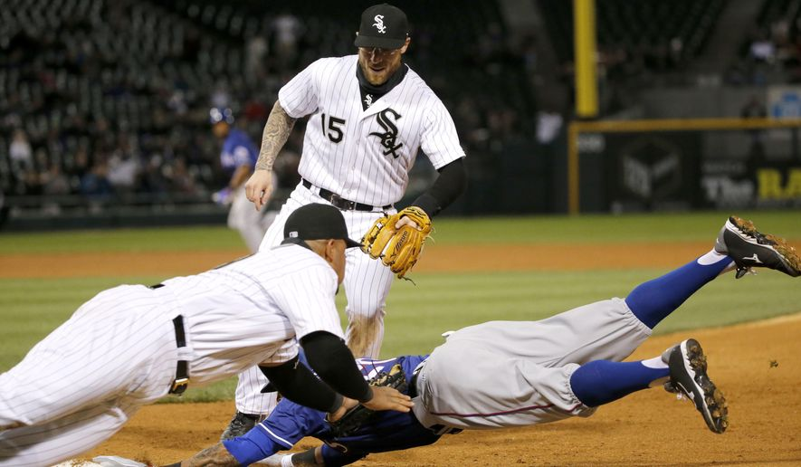 Chicago White Sox first baseman Jose Abreu, front left, tags out Texas Rangers' Ian Desmond for the second out of a triple play with the bases loaded, during the seventh inning of a baseball game Friday, April 22, 2016, in Chicago. White Sox second baseman Brett Lawrie, top, watches the play. (AP Photo/Charles Rex Arbogast)