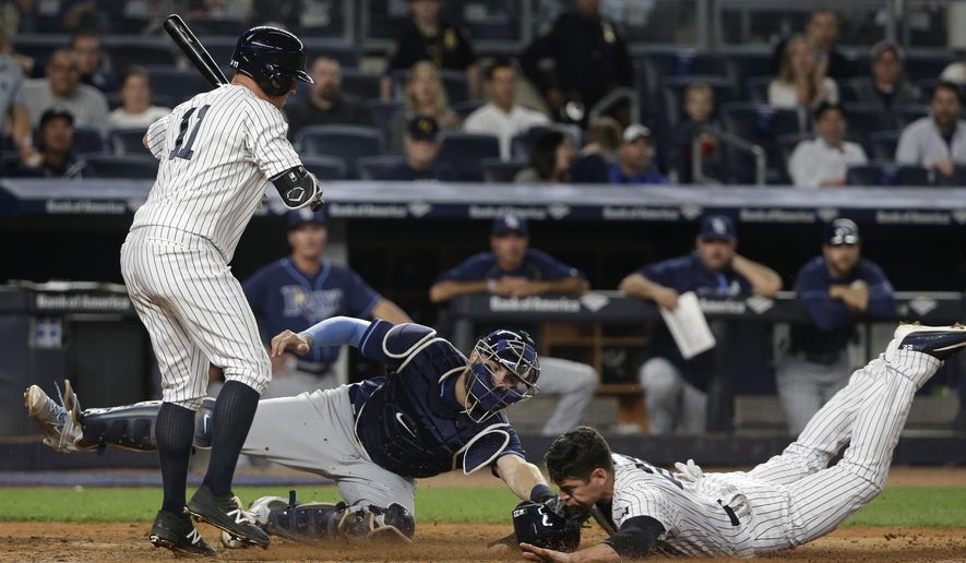New York Yankees' Jacoby Ellsbury slides under the tag from Tampa Bay Rays catcher Curt Casali (19) to steal home as Yankees' Brett Gardner (11) steps out of the way during the fifth inning of a baseball game, Friday, April 22, 2016, in New York. (AP Photo/Julie Jacobson)