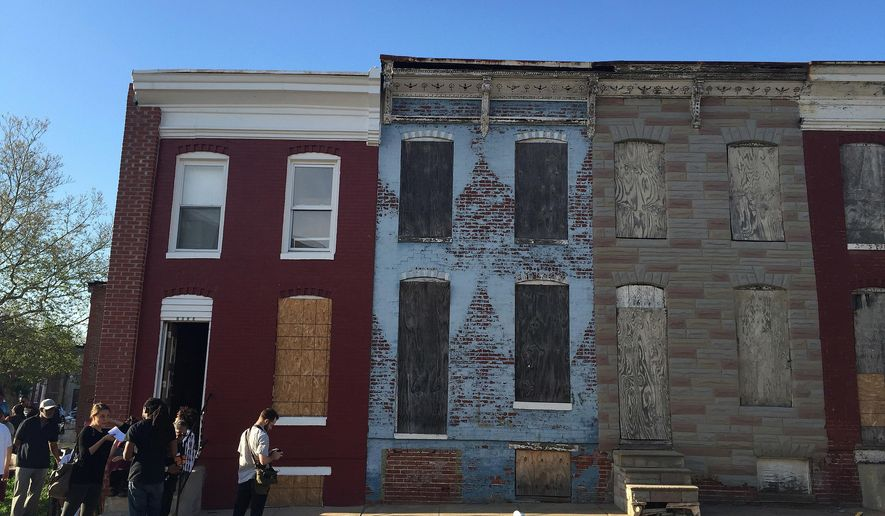 In this April 19, 2016, photo, community activists stand in front of a vacant home that they are transforming into a community center, which sits on a block of derelict buildings in the Sandtown-Winchester neighborhood in Baltimore, Md., just across from where Freddie Gray was arrested. (AP photo/Juliet Linderman)
