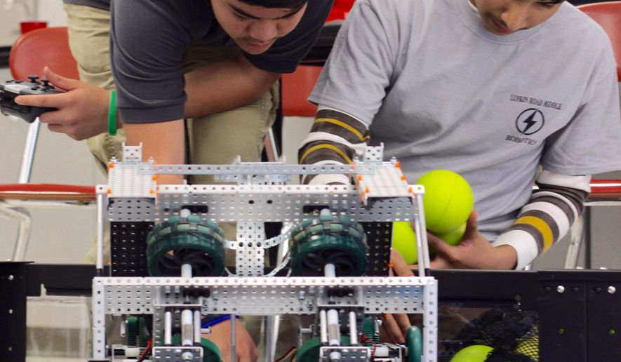 ADVANCED FOR RELEASE MONDAY, APRIL 25, 2016 Gargeori Sibelius and Shamyl Kahn, both eighth-graders, prepare the Lufkin Road Middle School's robot for a round of shooting practice at the school in Apex, N.C. The team qualified to compete at this year's Vex World Robotics Competition in Louisville, Ky., from April 20-23. (Henry Gargan/The News & Observer via AP)