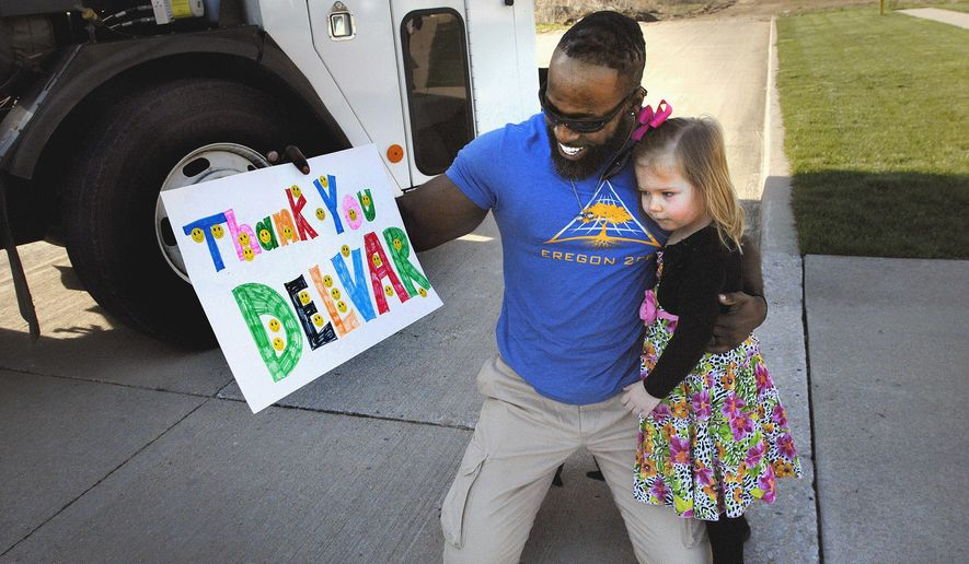 In this April 14, 2016 photo, Brooklyn Andracke, 3, gives Bloomington sanitation specialist Delvar Dopson a thank-you sign and a hug after Dopson stopped by the Andracke household to make a pickup with his garbage truck in Bloomington, Ill. Brooklyn has been waving to Dopson for a year and has developed a fascination with his garbage truck. (David Proeber/The Pantagraph via AP) MANDATORY CREDIT