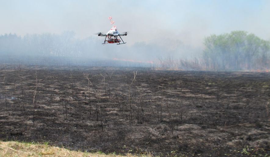 A drone designed to ignite controlled grass fires comes in for a landing in a field at the Homestead Monument of America in Beatrice, Neb., on Friday, April 22, 2016. University of Nebraska-Lincoln researchers are testing the drone as a possible tool for firefighters. (AP Photo/Grant Schulte)
