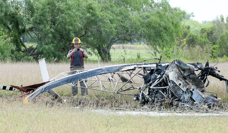 CORRECTS NAME OF VALLEY REGIONAL MEDICAL CENTER - A firefighter with the Los Fresnos, Texas Fire Department takes photographs of the scene where a helicopter crashed on Thursday, April 21, 2016, in Los Fresnos, Texas. Authorities state the helicopter made contact with nearby power lines, causing the pilot to lose control and crash in an open field. The pilot was taken to Valley Regional Medical Center in Harlingen, pending transfer to a burn ward in San Antonio. (Jason Hoekema/The Brownsville Herald via AP)