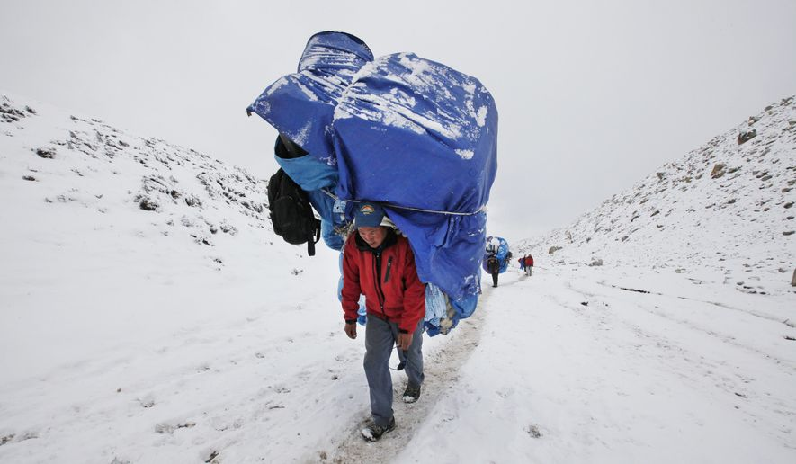 In this March 28, 2016 photo, a porter walks with a massive load towards Everest Base camp near Lobuche, Nepal. The April 2014 avalanche, which killed 13 Sherpa guides and three other Nepali workers, was an immense blow to the Sherpa community. Nearly all the surviving Sherpas refused to continue working that year, demanding, among other things, better working conditions, more insurance, and free education for the children of those killed. Over the past two years the government has enacted a series of policy changes, from stationing officials at Base Camp to creating a welfare fund for the families of the Sherpa dead, in large part to convince climbers and trekkers to keep coming back to Everest. (AP Photo/Tashi Sherpa)