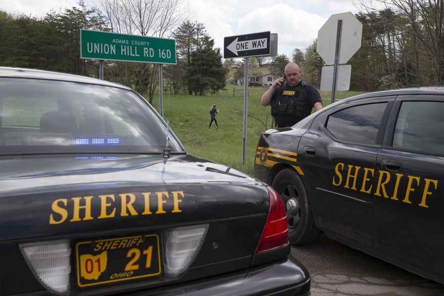 Authorities create a perimeter near a crime scene on Union Hill Rd, Friday, April 22, 2016, in Pike County, Ohio. Shootings with multiple fatalities were reported along a road in rural Ohio on Friday morning, but details on the number of deaths and the whereabouts of the suspect or suspects weren't immediately clear. (AP Photo/John Minchillo)