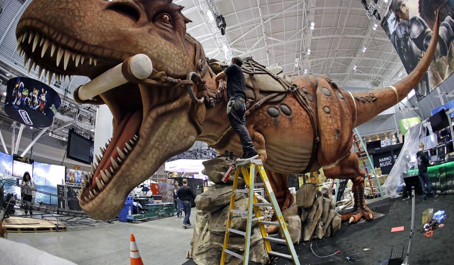 Joshua Patino stands on a ladder to put finishing touches on a giant dinosaur exhibit at PAX East in the Boston Convention and Expo Center, Thursday, April 21, 2016, in Boston. PAX East, an annual celebration of gaming culture, is expected to draw tens of thousands of visitors Friday through Sunday. It's a place where serious gamers can preview unreleased video games and devices, compete in tournaments, hear live music and meet others for whom gaming is a way of life. (AP Photo/Elise Amendola)