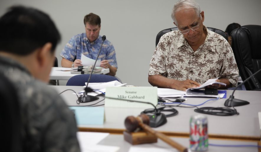 Hawaii Sen. Mike Gabbard met with lawmakers to discuss a bill that would give money to fight a deadly forest disease during a hearing at the State Capitol on Friday, April 22, 2016, in Honolulu. Also known as rapid ohia death, the disease has infected thousands of acres of native forests on the Big Island and is quickly spreading. (AP Photo/Marina Riker)