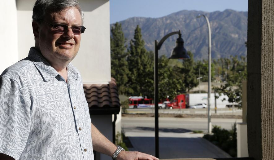 In this Thursday, March 17, 2016, photo, Robert Leviton poses for a photo on the balcony of his townhouse in Pasadena, Calif. The traffic on the stretch of highway, background, that runs alongside his complex creates a persistent din and is visible from any of his townhome's north-facing windows. Leviton knew it would be like this when he bought the two-bedroom unit for $666,000 last summer. (AP Photo/Nick Ut)