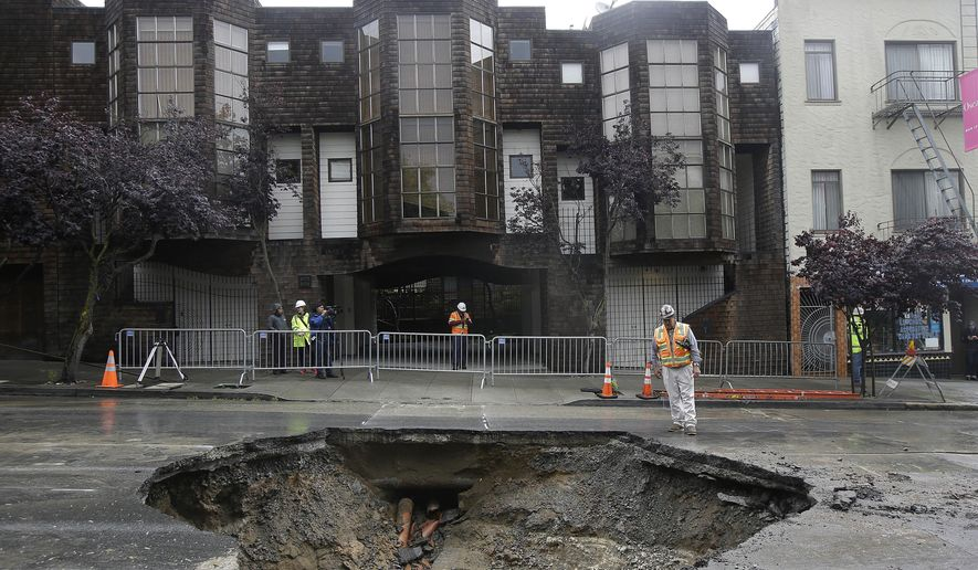 A San Francisco Public Utilities Commission worker stands over a large sinkhole on Sacramento Street in San Francisco, Friday, April 22, 2016. According to a spokesperson for the the city's Public Utilities Commission, the sinkhole appeared on Thursday, caused by a broken sewer pipe line. (AP Photo/Jeff Chiu)