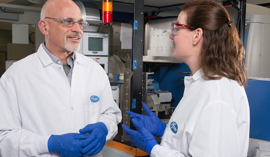 """This April 13, 2016, photo provided by Pfizer shows Pfizer Discovery Medicinal Chemists Jotham Coe, left, and Jennifer Young in Groton, Conn. Seven years after U.S. regulators slapped their strictest warning on two popular smoking-cessation medicines, citing risks of suicidal behavior, a large international study found no such risk. Now Chantix maker Pfizer and Zyban maker GlaxoSmithKline hope the Food and Drug Administration, which ordered them to do the study, will remove the so-called """"black box warnings"""" put on their prescription drugs due to anecdotal patient reports of serious psychiatric side effects. (Pfizer via AP) MANDATORY CREDIT"""