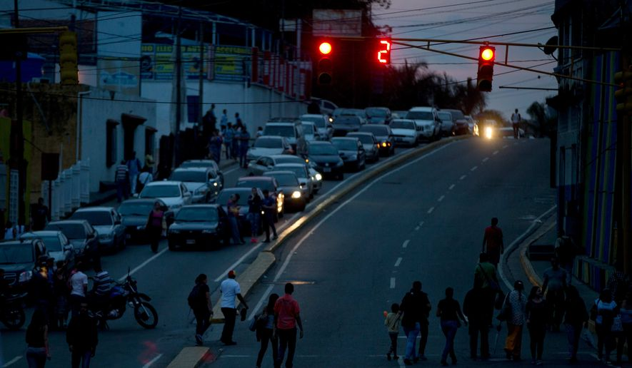 Pedestrian and drivers are blocked by a protest of the residents of municipality El Hatillo, who are blocking the streets around their neighborhood after 24 hour without electricity just outside of Caracas, Venezuela, Saturday, April 23, 2016. The power outages have compounded other problems of daily life. The country is already among the most violent in the world, and streets become doubly scary when pitch black. Power outages also knock out service from the water tanks with electric pumps that many Venezuelans use to deal with chronic cuts to running water.(AP Photo/Fernando Llano)