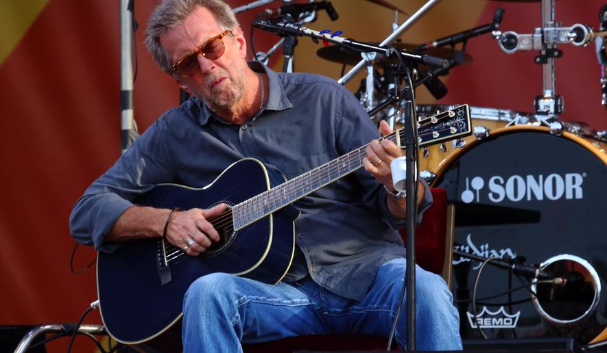 """FILE - In this April 27, 2014 file photo, Eric Clapton performs at the 2014 New Orleans Jazz & Heritage Festival at Fair Grounds Race Course  in New Orleans. Clapton is sharing his grief over Prince's death, calling him """"a true genius."""" In a Facebook post Saturday, April 23, 2016,  Clapton also tells how the artist inspired him to write the song """"Holy Mother.""""(Photo by John Davisson/Invision/AP)"""