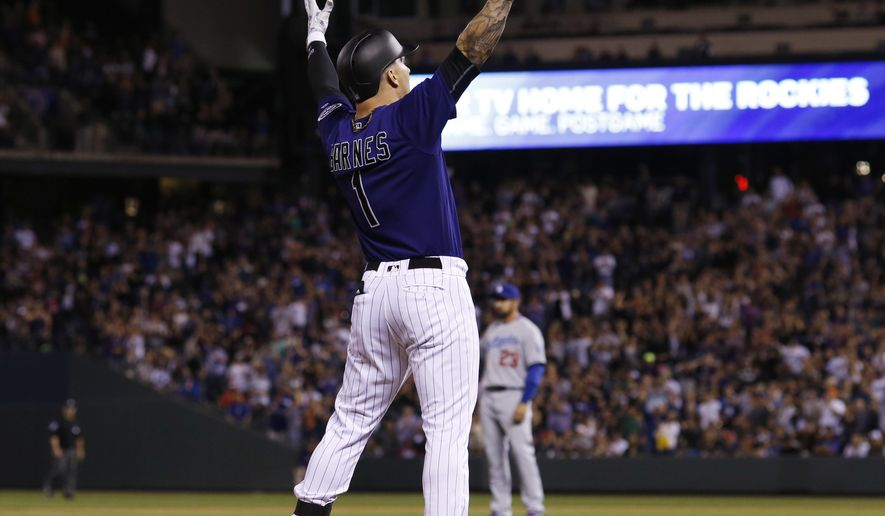 Colorado Rockies' Brandon Barnes celebrates at third base with a two-run triple off Los Angeles Dodgers relief pitcher Chris Hatcher in the eighth inning of a baseball game Friday, April 22, 2016, in Denver. Colorado won 7-5. (AP Photo/David Zalubowski)