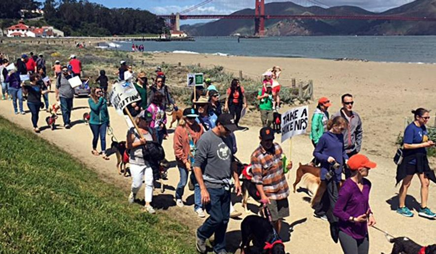 """Hundreds of dog owners march with their four-legged pooches to protest the National Park Service's proposed limits on dog walking at Crissy Field in San Francisco's Golden Gate National Recreation Area Saturday, April 23, 2016. Many held signs saying """"Unleash Our Land!"""" and """"Put Feds On A Leash!""""  (Kevin Schultz/San Francisco Chronicle via AP)  MANDATORY CREDIT PHOTOG & CHRONICLE; MAGS OUT; NO SALES"""
