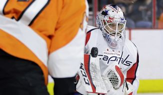 Washington Capitals' Braden Holtby, right, blocks a shot as Philadelphia Flyers' Wayne Simmonds looks for the rebound during the second period of Game 6 in the first round of the NHL Stanley Cup hockey playoffs, Sunday, April 24, 2016, in Philadelphia. Washington won 1-0 and won the series, 4-2. (AP Photo/Matt Slocum)