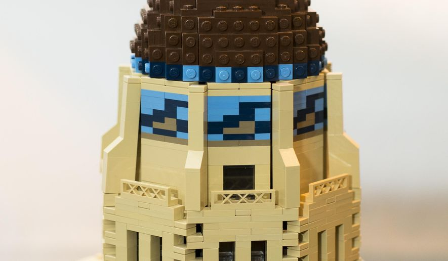 ADVANCE FOR WEEKEND EDITIONS APRIL 23-24 - In this Thursday, April 7, 2016, photo, John Tooker used 25,755 specially ordered LEGO bricks to construct a replica of the Nebraska State Capitol, in Lincoln, Neb. He started in grad school, buying bulk bags of tan bricks when his budget allowed and piecing them together over the course of five years. John Tooker's Nebraska State Capitol now stands 3 feet tall, and consists of 25,755 bricks. It's 1/140th the size of the actual building, with Lego landscaping that's accurate down to the single bush. (Matt Ryerson/The Journal-Star via AP) LOCAL TELEVISION OUT; KOLN-TV OUT; KGIN-TV OUT; KLKN-TV OUT; MANDATORY CREDIT