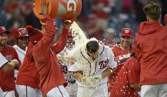Washington Nationals center fielder Chris Heisey, center, is doused with liquid after he hit a walk off home run during the 16th inning of an interleague baseball game against the Minnesota Twins, Sunday, April 24, 2016, in Washington. The Nationals won 6-5 in 16 innings. (AP Photo/Nick Wass)