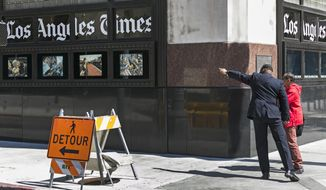 A pedestrian asks for directions outside the Los Angeles Times building in downtown Los Angeles, Monday, April 25, 2016. Newspaper publisher Gannett said Monday that it wants to buy rival Tribune Publishing in a deal that would give the owner of USA Today control of the Los Angeles Times, Chicago Tribune and several other newspapers. (AP Photo/Damian Dovarganes)