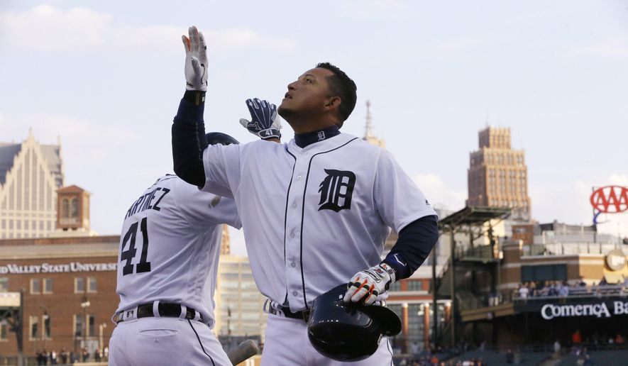 Detroit Tigers' Miguel Cabrera looks skyward after a high five from designated hitter Victor Martinez (41) after scoring on a solo home run during the first inning of a baseball game against the Oakland Athletics, Monday, April 25, 2016 in Detroit. (AP Photo/Carlos Osorio)
