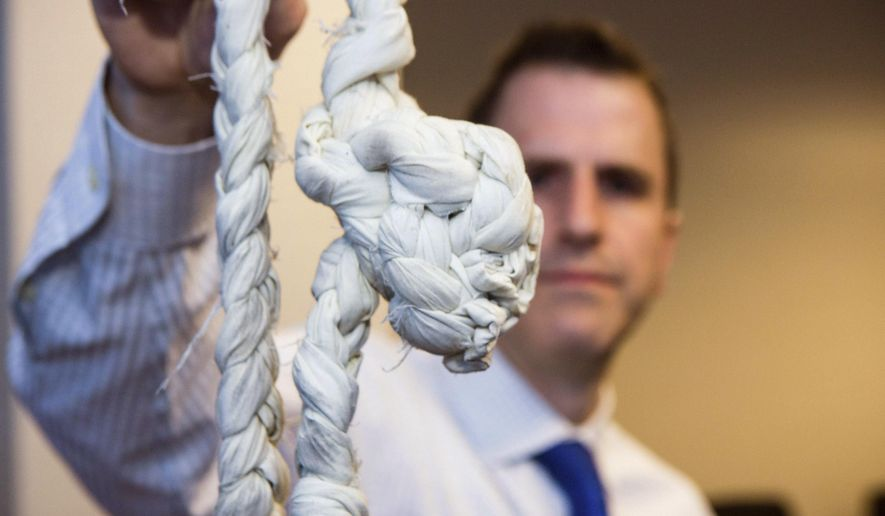 In this April 18, 2016 photo, Garrett Croon holds up a rope at FBI headquarters in Chicago that two bank robbers used to escape from Chicago's Metropolitan Correctional Center in 2012. FBI special agent Timothy E. Bacha says he hopes to send the rope, along with concrete and a metal bar from the cell that housed the pair, to be displayed at the FBI Education Center in Washington. (James Foster/Chicago Sun-Times via AP) MANDATORY CREDIT, MAGS OUT, NO SALES; CHICAGO TRIBUNE OUT