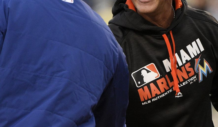Miami Marlins manager Don Mattingly, left, shakes hands with Los Angeles Dodgers manager Dave Roberts, right, as they meet at home plate prior to a baseball game in Los Angeles, Monday, April 25, 2016. (AP Photo/Kelvin Kuo)
