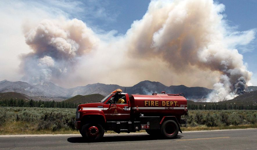 FILE - This July 16, 2013 file photo a water tender makes his way back to the the Mountain Fire near Lake Hemet. Vast wildfires have created lengthy gaps in Southern California sections of the famed Pacific Crest Trail, which hikers must bypass via shuttles or alternate routes to avoid dangerous conditions like unstable trees and loose rocks. (Frank Bellino/The Press-Enterprise via AP)